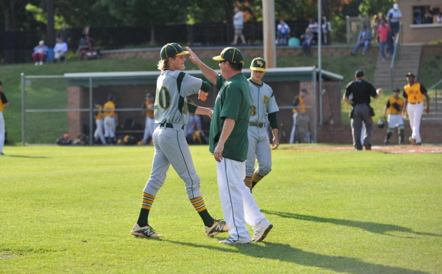 Coach+Kinney+greets+senior+Scout+Cox+as+they+finish+the+inning.+Kinney+always+brought+a+smile+to+his+players+faces+with+kind+words+as+they+ran+off+the+field.+