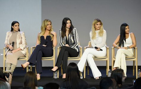 The Kardashians sit together at a conference.