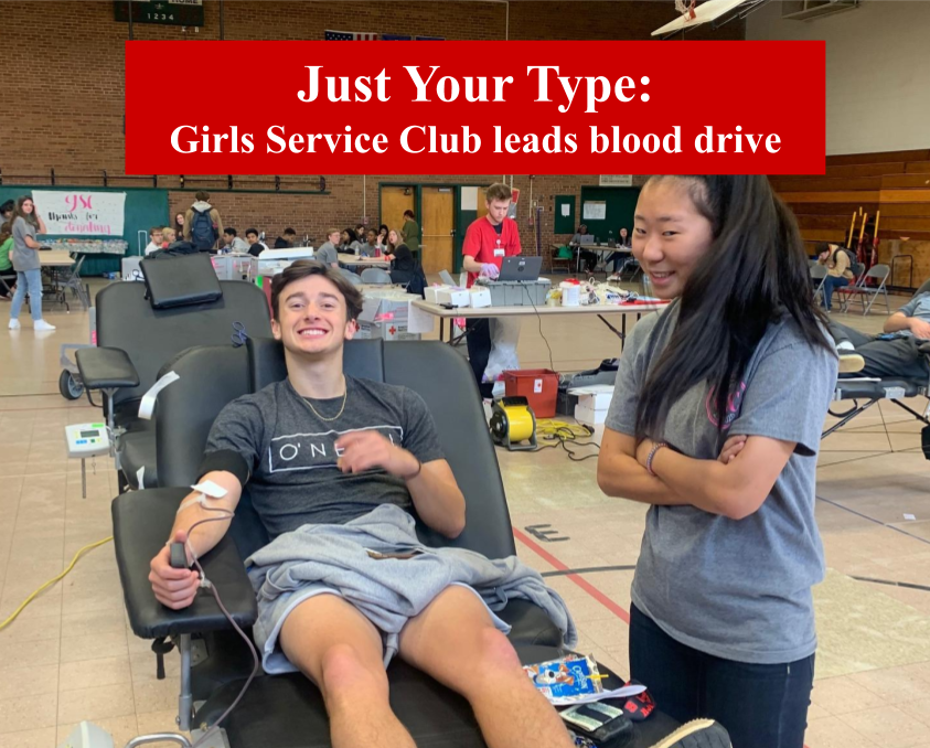 Girls Service Club member junior Chloe Christensen helps senior Max Fuehrer donate blood. Girls Service Club helps out the American Red Cross with their efforts to save lives.