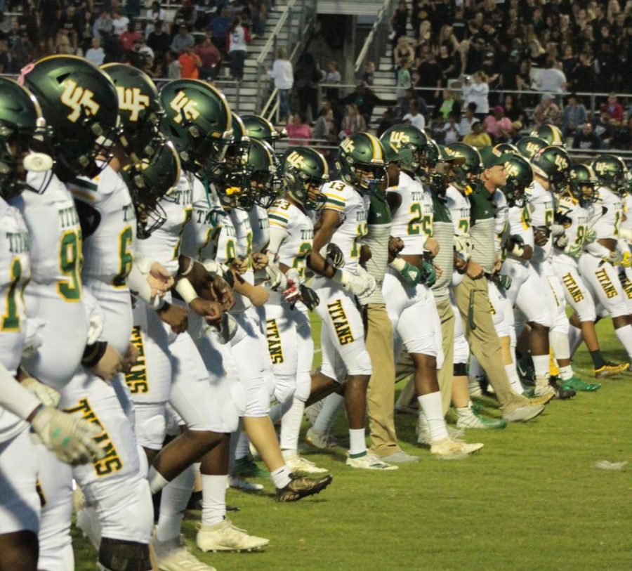 Varsity football players stand united as they prepare to take on the East Forsyth Eagles last fall. The Titans hope to play a condensed season in February.