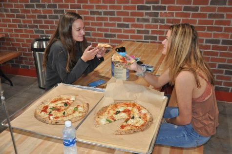 Seniors Caroline Adams (left) and Kellen Gentry (right) enjoy their first meal at the Cugino Forno in Clemmons. The restaurant was excited to finally open last week.