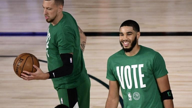 Celtic's players Daniel Theis (left) and Jayson Tatum (right) warm-up before a game in