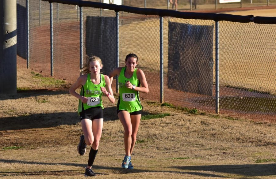 Freshman Lily Douglass (left) and Junior Kelly Smith (right) head into the final stretch at the cross country meet at Ivey Redmond on Dec. 5