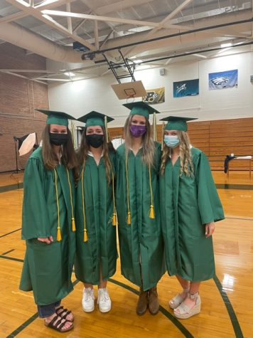 Seniors Caroline Adams (left), Jessica Martin, Alex Bryant and Emma Fiorani enjoy some time to catch up during cap and gown photos. Being unable to see each other at school like they once did, seniors are excited to seize any opportunity to spend time with classmates.