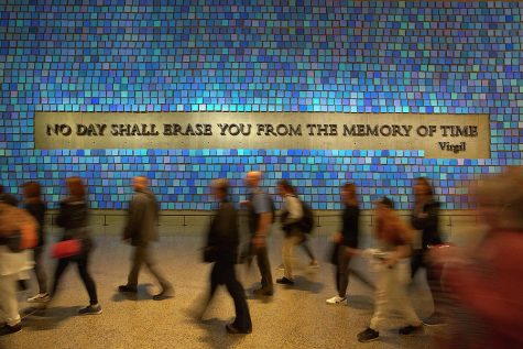 A quote by Virgil is the centerpiece in a sea of blue squares, each one memorializing a life lost on 9/11.