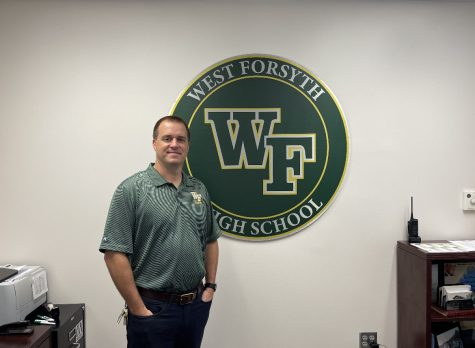 Principal Kevin Spainhour standing by the West Forsyth emblem in his office showing his Titan pride.