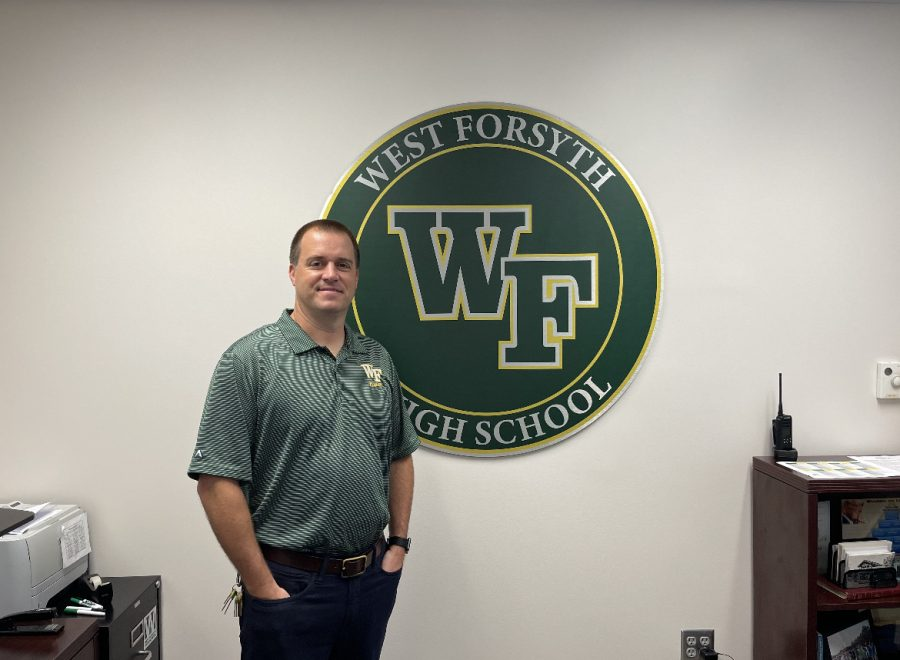 Principal+Kevin+Spainhour+standing+by+the+West+Forsyth+emblem+in+his+office+showing+his+Titan+pride.+